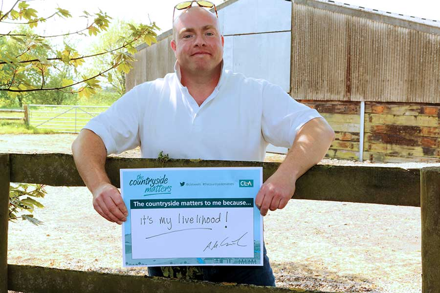 """Alex Carson-Taylor holds a printed sign which reads: """"The countryside matters to me because..."""" On the sign Mr Carson-Taylor has written: """"It's my livelihood."""""""