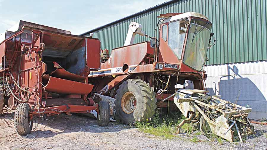 A Laverda combine sits in a yard to be used for spares