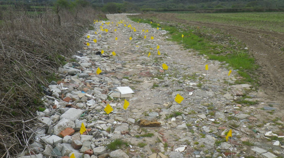 Yellow flags mark the spots where asbestos was found on farmland