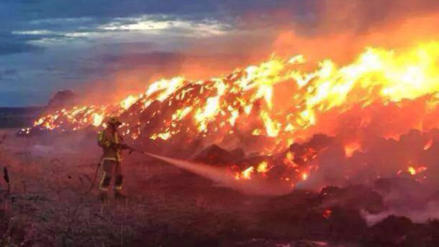 A firefighter battling a blaze on a Shropshire farm