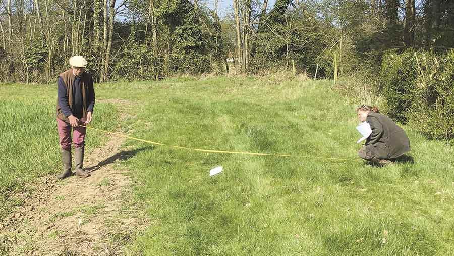 Two people measure buffer strips in a field