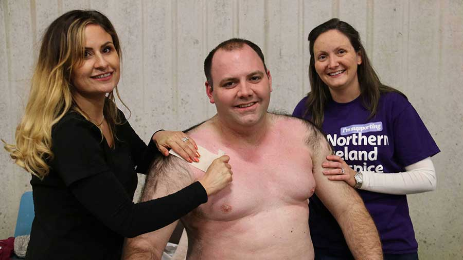 Kerry Reynolds stands next to a shirtless Samuel Steele. Kerry is holding a waxing strip. Mr Steele's wife, Naomi, stands next to him