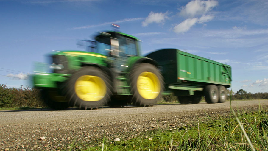 A tractor tows a trailer on the road