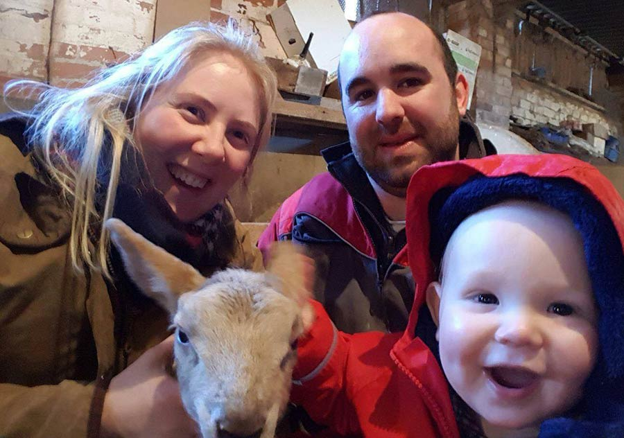 Young farming family with lamb