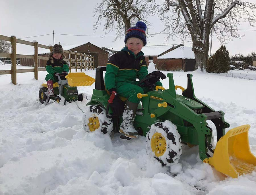 Children on ride on tractors in snow