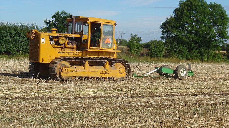 A Caterpillar tractor pulls a mole plough