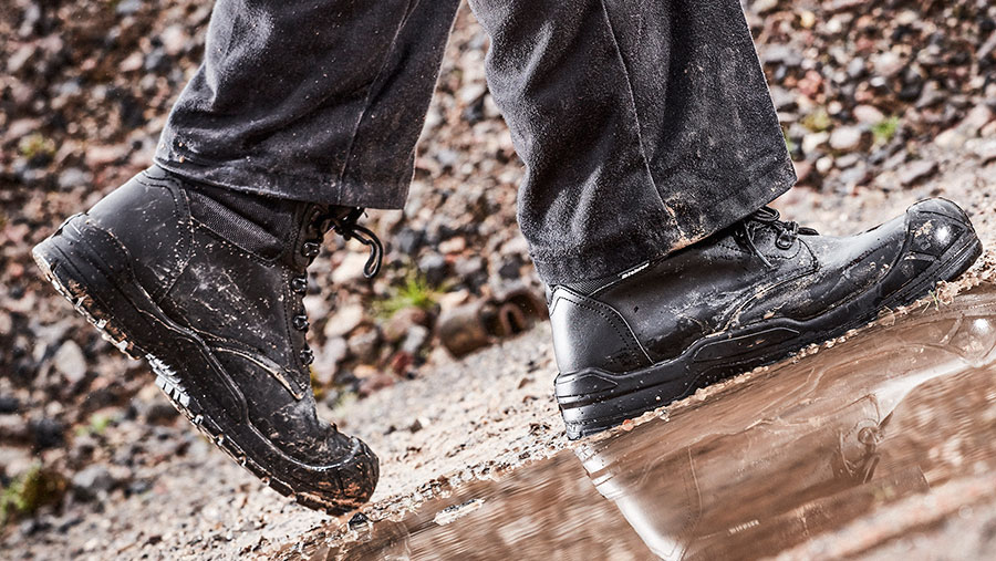A close up on the feet of a person wearing the Andover boot while walking through a muddy puddle
