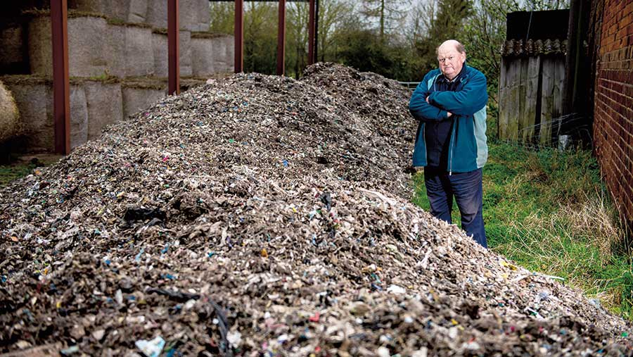 Andrew Nicholls stands next to a huge pile of fly-tipped waste