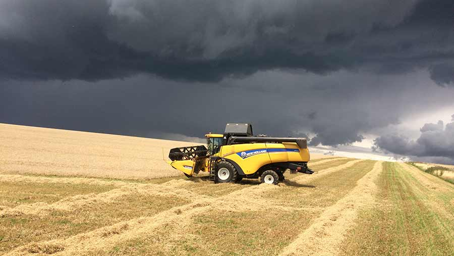 Combine in field under dark clouds