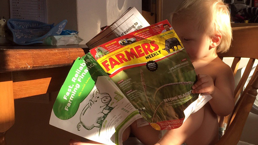 18-month-old Ted reads a copy of Farmers Weekly