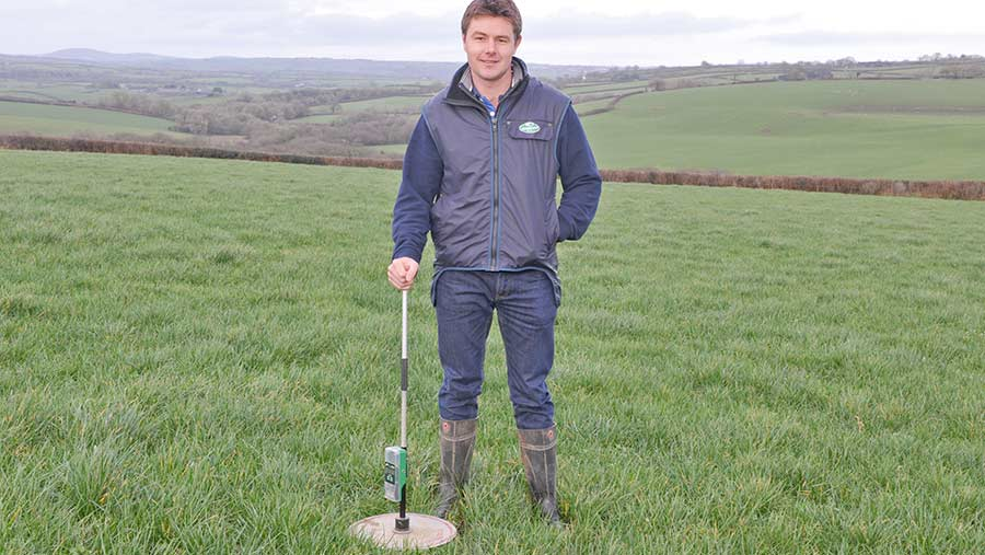 Rhys James with a plate meter in a paddock