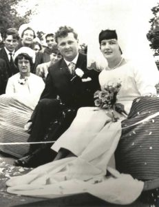 A black-and-white photograph shows Christine and David in their wedding outfits sat in a car while family and friends stand nearby