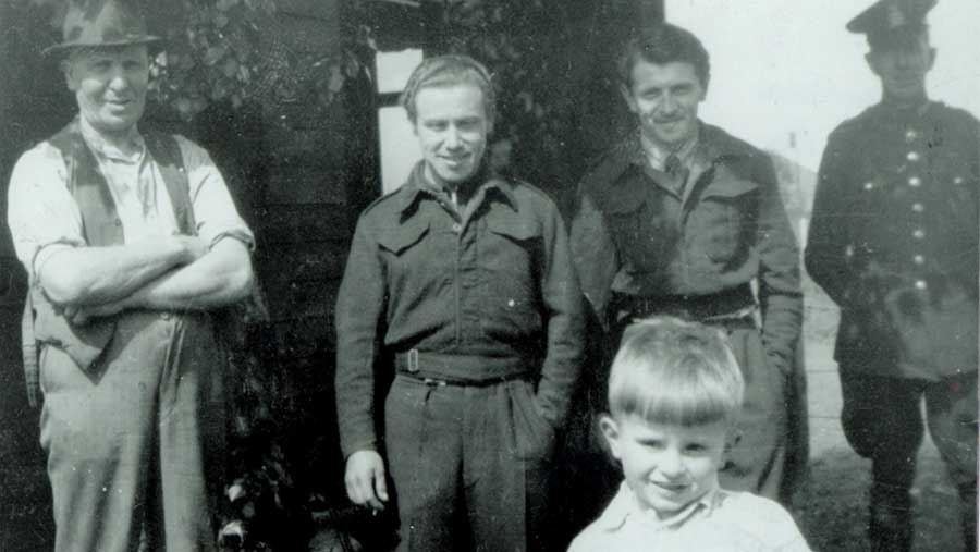 A young John Farnworth stands in the foreground of a black-and-white photograph with four man standing behind him