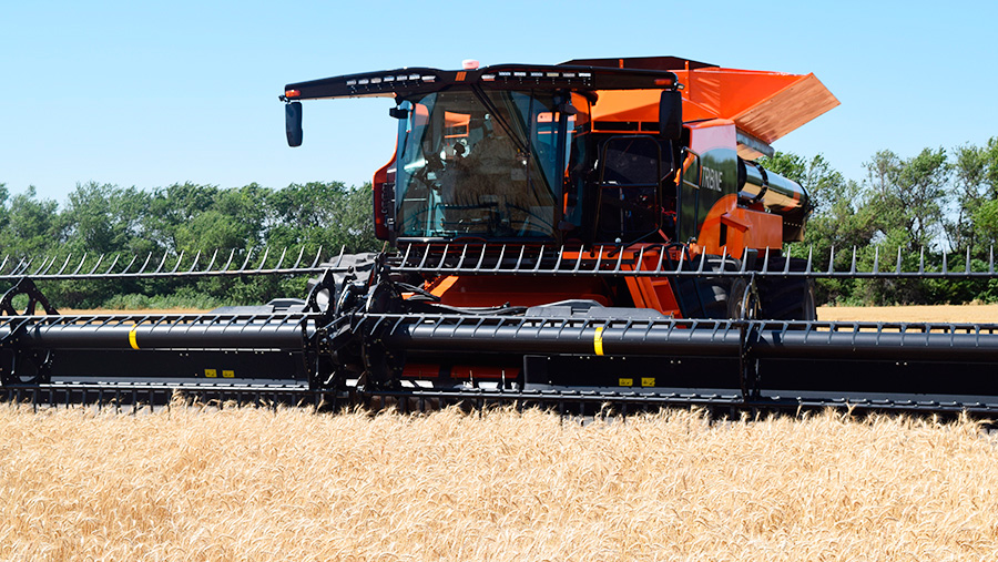 A Tribine combine harvester works in a field