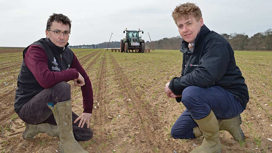 Matthew and Nick squat in a field with a tractor behind them