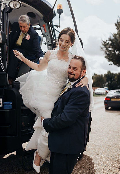 Harriet Hayward climbing out of a tractor in her wedding dress