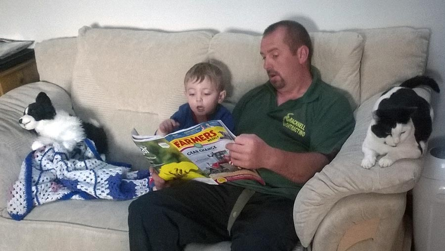 Father and son reading Farmers Weekly