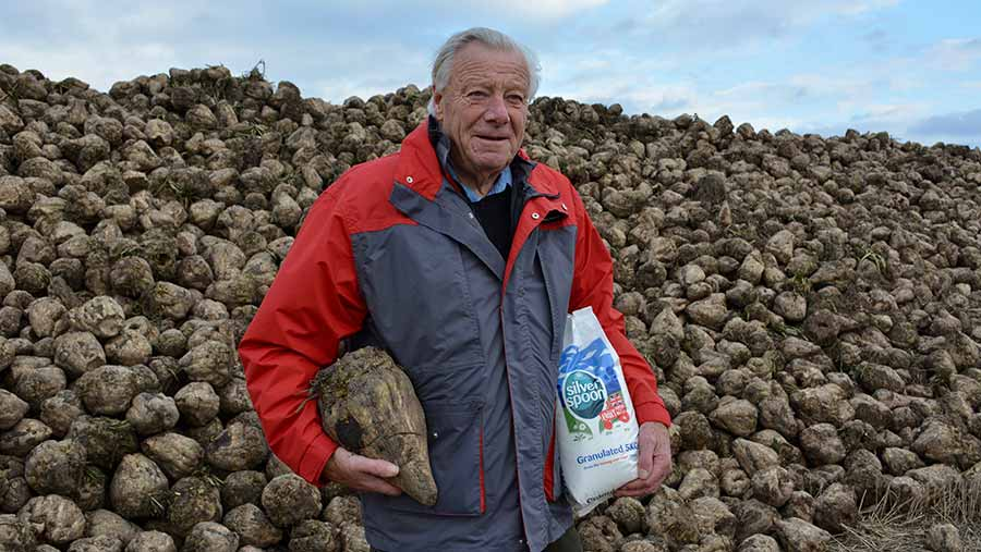 David Partridge with Silver Spoon sugar bag in front of heap of sugar beet