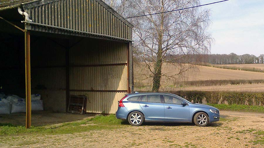 Man in Volvo driving out of grain shed