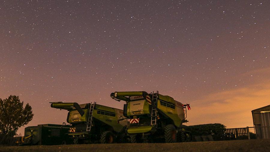 Claas combines under night sky