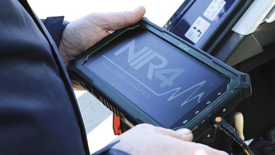 A farmer holds a tablet computer