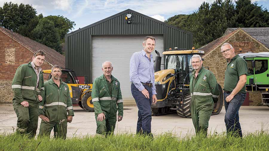 Chris Baylis stands in a field with his farm's staff