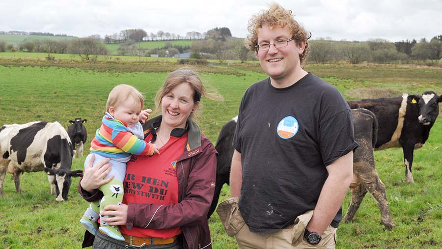 Liam and Annie James stand in a field of dairy cows. Annie holds infant daughter Buddug