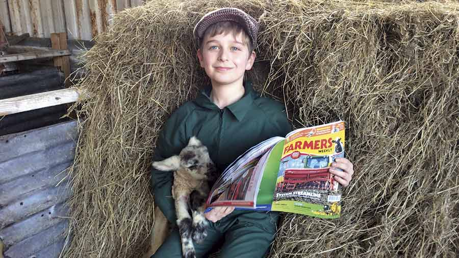 A boy stands next to a bale holding a lamb in one hand and a copy of Farmers Weekly in the other