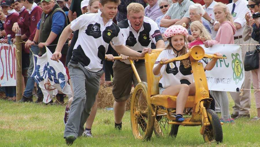 Young farmers push another along a field on a kart