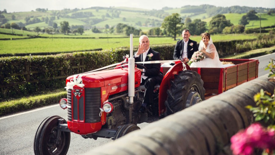 Bryan Gittins driving MF65 tractor with newly-weds in a trailer