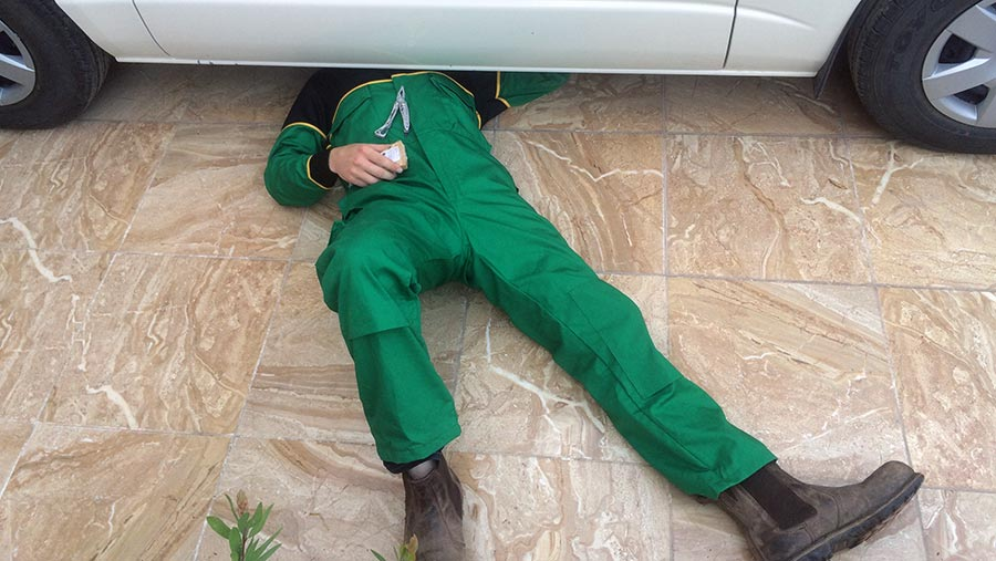 Roger wearing his John Deere overalls while fixing a car