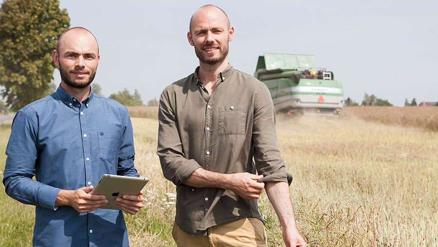 Anders and Søren Knudsen stand in front of a combine
