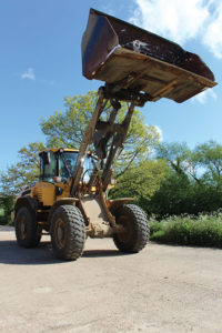 A Volvo loading shovel works in a yard