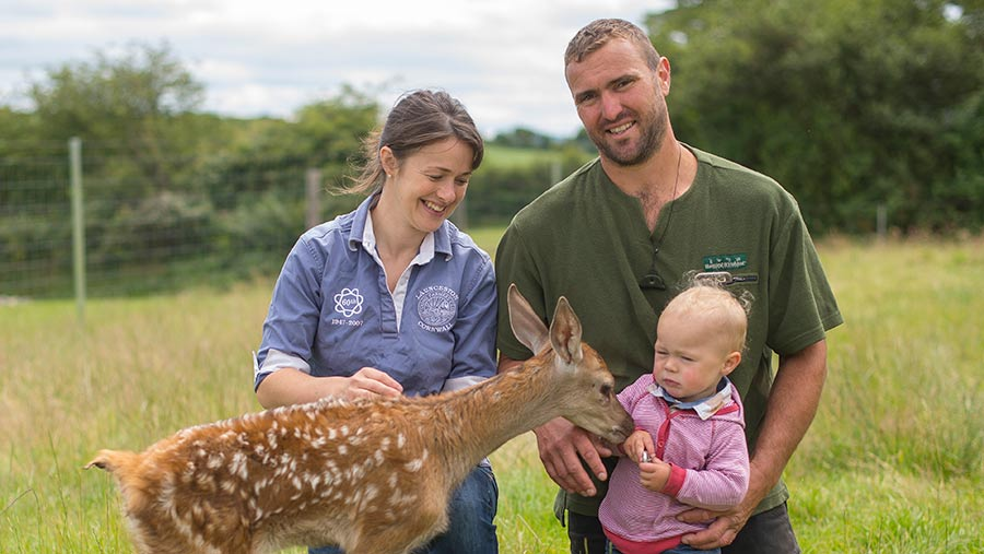 Pip and Matt Smith stand in a field with their young son Dusty and a deer