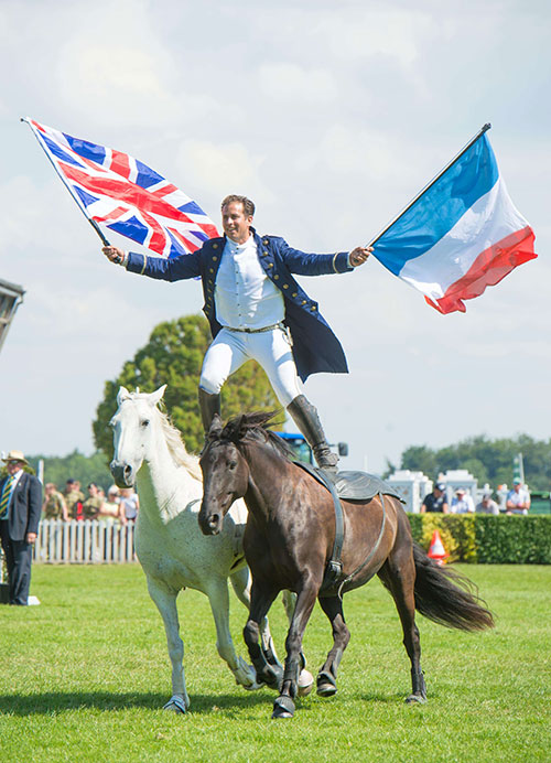 Lorenzo stands balanced on two moving horses carrying a Union flag in one hand and the Tricolour in the other