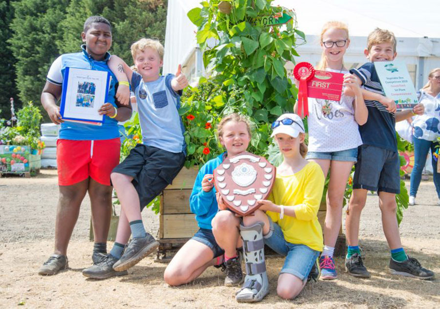 Six pupils pose for the camera holding a certificate and plaque for the Great Yorkshire Show's veg box challenge