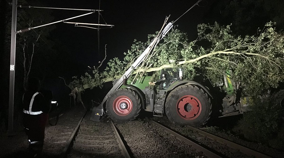 A tractor and trailer on railways tracks. An uprooted tree lies across the cab