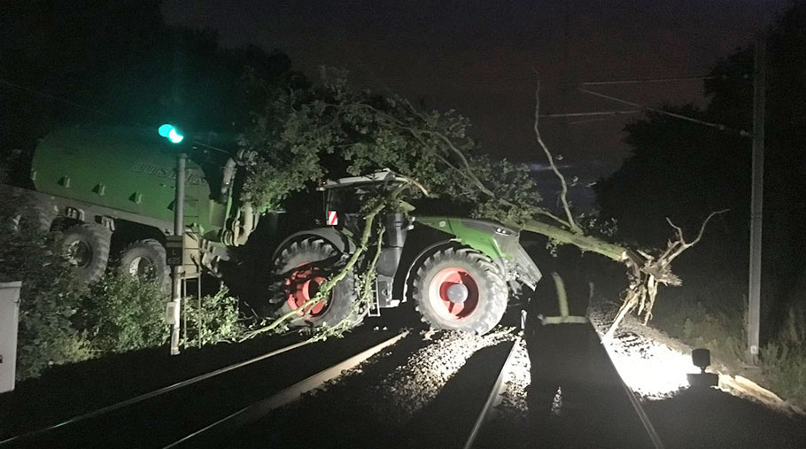 A tractor and trailer on railway tracks. An uprooted tree lies across the cab