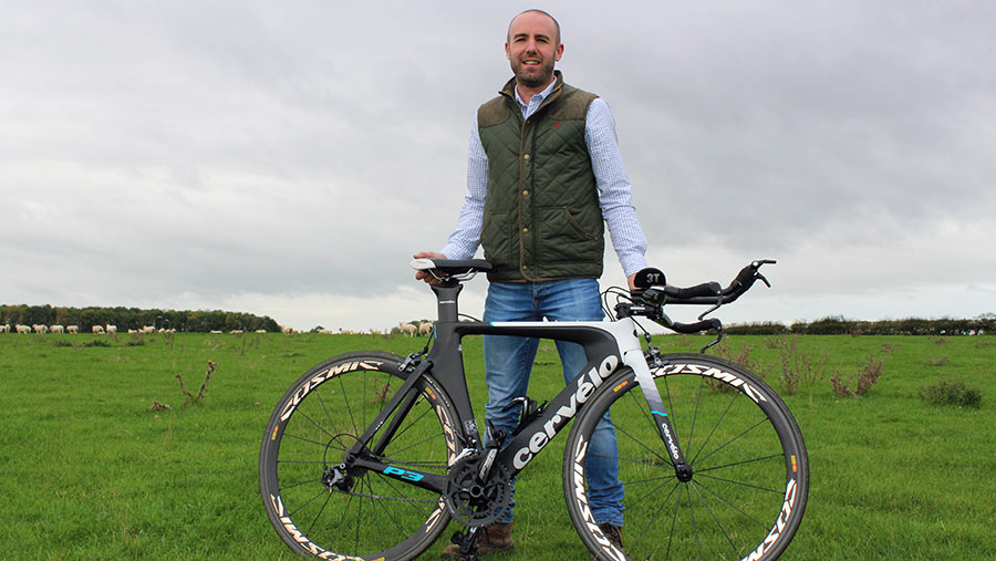 Adam Madge with his racing bike in a field of sheep