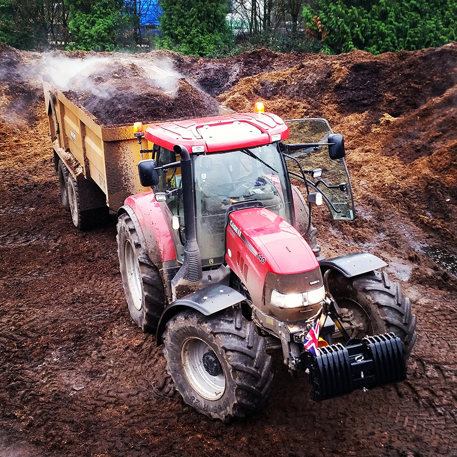 A tractor pulls a trailer of muck