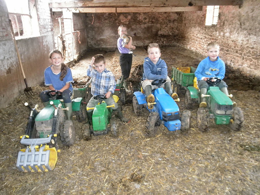 A group of children sit on toy tractors while one stands behind holding a cat