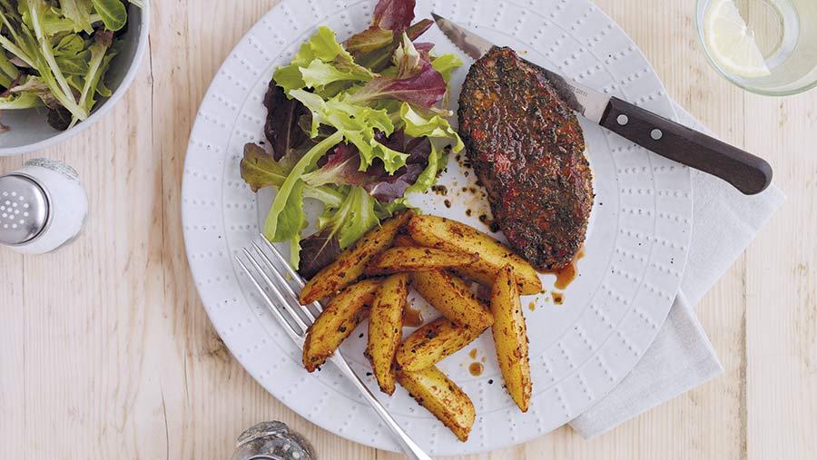 Lamb leg steaks wit paprika rub on a plate with potato wedges