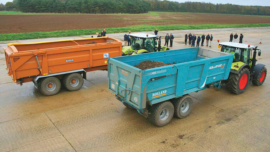 Two tractors each pulling a trailer have their brakes tested as a crowd of people watch
