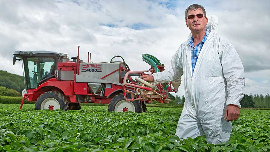 Richard Fox standing with a sprayer in a field