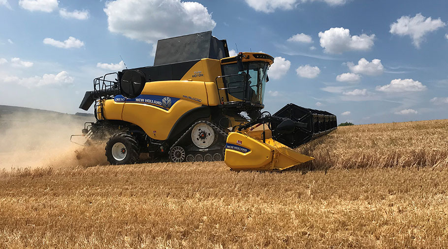 A combine harvester works in a field of winter barley