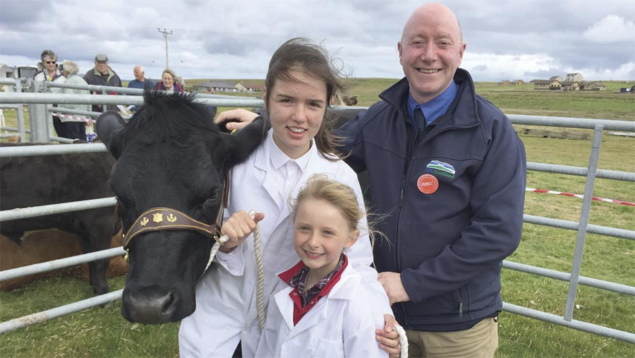Gary Mitchell with Emma Burgess and Anja Leslie, pictured with Emma's heifer calf, Smartie