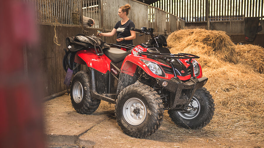A woman feeds a horse in a barn. In the foreground is a Kymco MXU 300 ATV