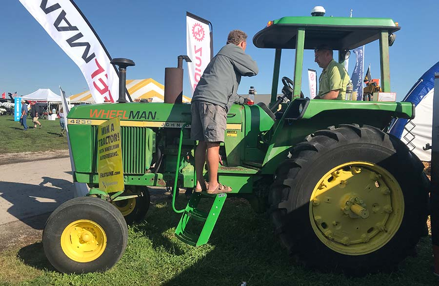 Visitors inspect a John Deere 4230 tractor at the show