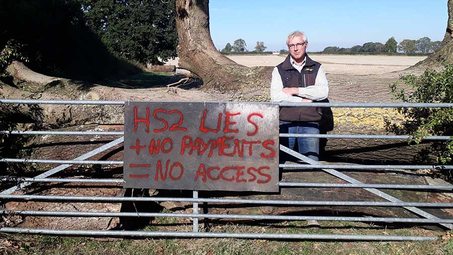 Farmer Sam Burton behing gate with protest sign