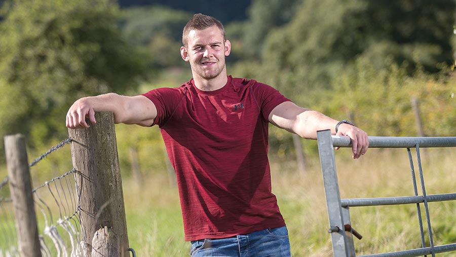 Rugby player Dan Lydiate stands by a gate on his farm